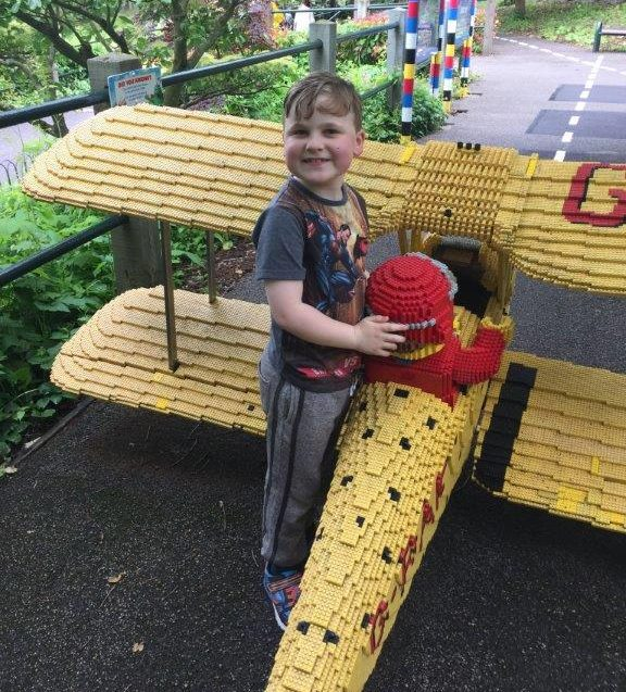 Boy next to lego model